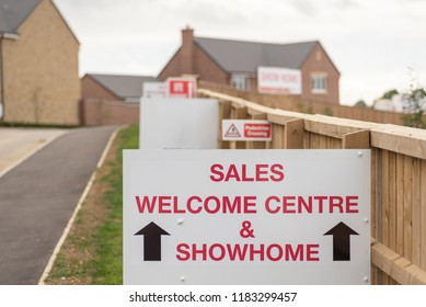 Sales welcome centre and showhome sign on new residential homes development estate entrance in England