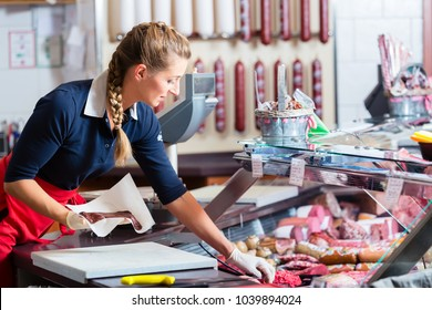 Sales woman in butcher shop putting different kinds of meat and sausage in display