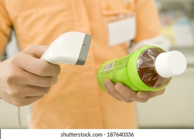salesclerk of convenience store scanning bar code