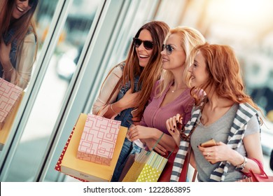 Sale,shopping, travel and people concept-happy friends with shopping bags in the city.