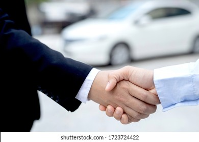 Salesman agrees to join hands to buy-sell car in the showroom.