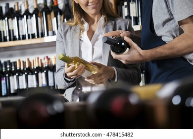 Salesman Assisting Female Customer In Choosing Wine