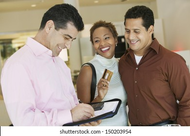 Salesman calculating bill while couple holding credit card in furniture store