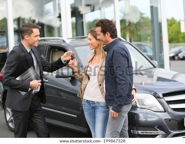 Salesman in car dealership giving keys to clients