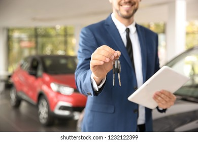 Salesman with car keys and tablet in auto dealership, closeup