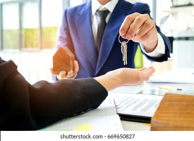 Salesman carrying a model house in hand is delivering the house key to the buyer,Customers receive home keys from home sales sales,Deliver house keys between seller and buyer.Home sales concept image.