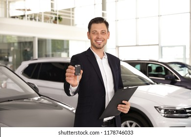 Salesman with clipboard and car key standing in salon