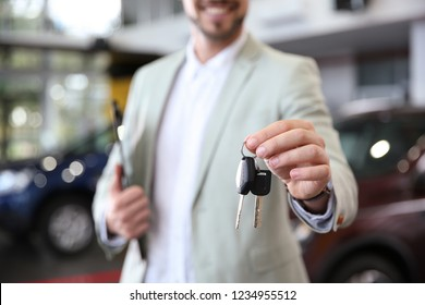 Salesman with clipboard and car keys in modern auto dealership, closeup