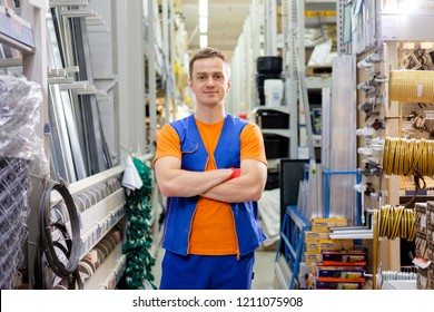 salesman at construction super store standing with crossed hands and smiling