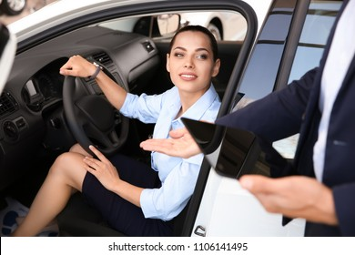 Salesman consulting young woman in auto at car dealership