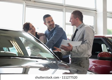 Salesman and a couple looking at a car in a car shop