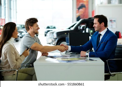 Salesman and customer shaking hands congratulating each other at the dealership showroom.