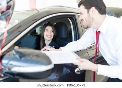 Salesman with financial document talking to client sitting in new car at showroom