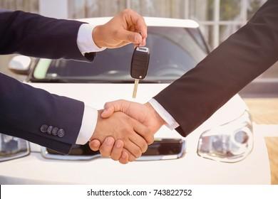 Salesman giving car key to customer outdoors