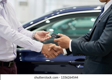 Salesman giving car keys to customer and shaking his hand