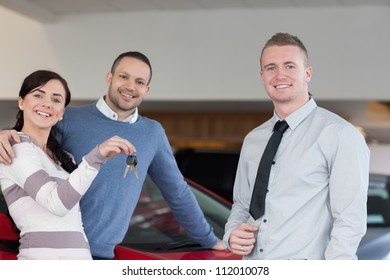 Salesman giving keys to an embracing couple in a car shop