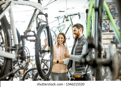 Salesman helping young woman to choose a new bicycle to buy standing in the bicycle shop