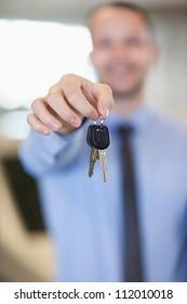 Salesman holding car keys by his fingertips in a dealership