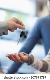 Salesman holding keys over the hand of a customer in a car-shop