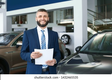 Salesman in modern car showroom