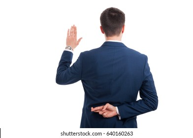Salesman promising an oath with crossed fingers behind his back as false statement concept isolated on white background