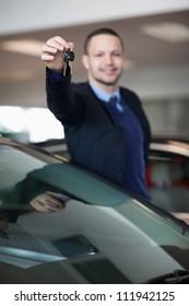 Salesman raising his arm while holding car keys in a dealership