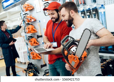 Salesman in red shirt and baseball cap is showing bearded client new chainsaw explaining details on laptop in power tools store.
