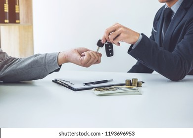 Salesman send key to customer after good deal agreement, successful car loan contract buying or selling new vehicle.