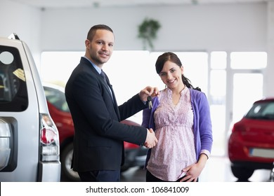 Salesman shaking hand and giving keys to a woman in a car shop