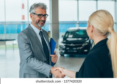 Salesman shaking hands with customer in car dealership showroom