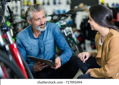 salesman showing bicycle parts to woman