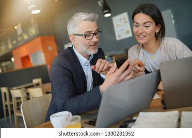 Salesman showing cellphone to manager during informal breakfast meeting