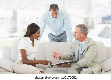 Salesman showing clients where to sign the contract in the office