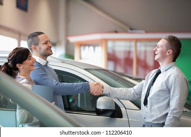 Salesman smiling while shaking the hand of a customer in a car shop