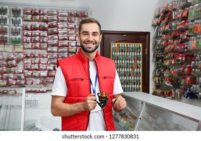 Salesman with spinning reel in sports shop. Fishing equipment