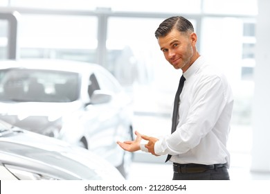 Salesman Standing at the Car Showroom and Showing New Cars