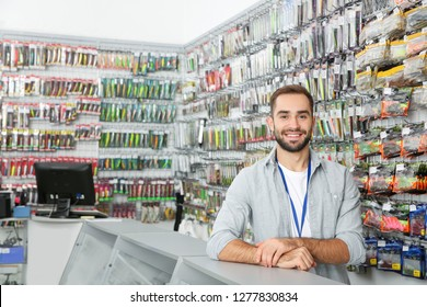 Salesman standing near showcase with fishing equipment in sports shop. Space for text