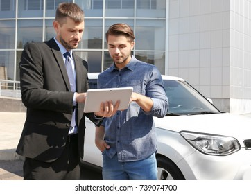 Salesman with tablet and client standing near new car outdoors