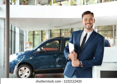 Salesman with tablet in modern car dealership