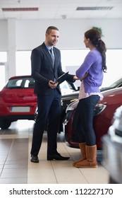 Salesman talking to a customer in a car shop
