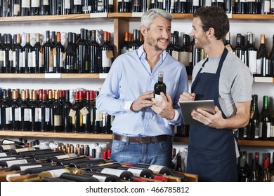 Salesman Using Digital Tablet While Customer Holding Wine Bottle