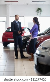 Salesman and a woman talking next to a car in a car shop