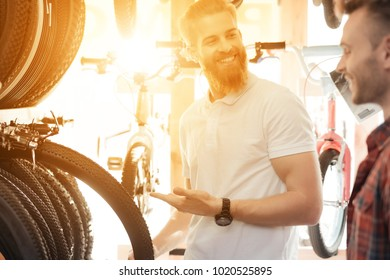 A salesperson at a bicycle store helps a young buyer choose tires for a bicycle. A man with a beard shows the client different types of goods. They both have a good mood.