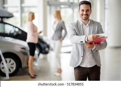 Salesperson at car dealership selling vehichles
