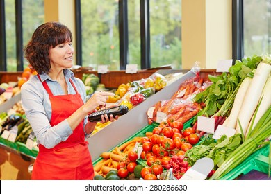 Salesperson counting vegetables with mobile data registration terminal for a new delivery in a supermarket