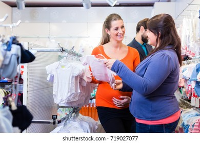 Salesperson with couple buying baby clothes in shop, the woman is pregnant