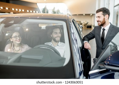 Salesperson with couple choosing a new car in the showroom