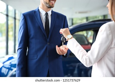 Salesperson giving car keys to man in auto dealership, closeup