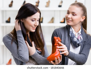 Salesperson offers footwear for the female customer in the shopping center