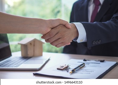 The salesperson shake hands with the landlord after negotiating a living agreement.